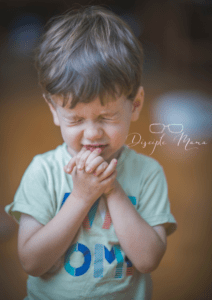 toddler boy with eyes closed and hands folded in prayer | Disciple Mama