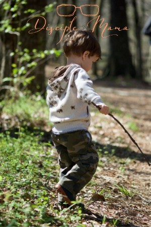 A toddler boy walking in the woods, holding a stick- outdoor play for toddlers | Disciple Mama
