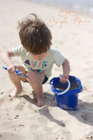 Toddler playing in sand with a shovel and bucket | Disciple Mama